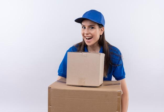 Giovane ragazza di consegna in uniforme blu e cappuccio che tiene le scatole di cartone che guarda l'obbiettivo che sorride ampiamente, felice ed uscito