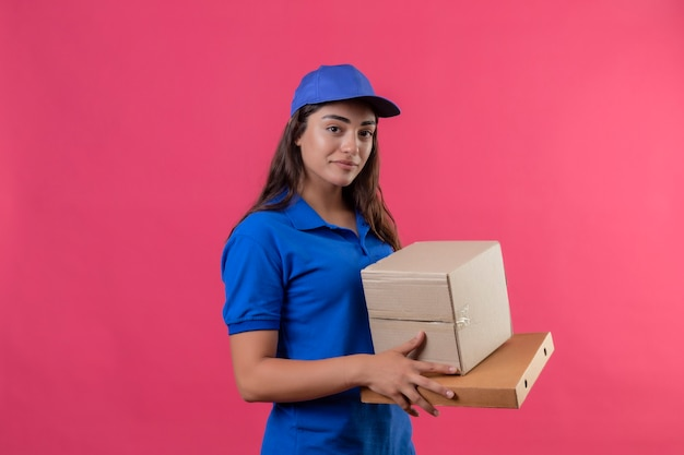 Young delivery girl in blue uniform and cap holding cardboard boxes smiling confident positive and happy standing over pink background