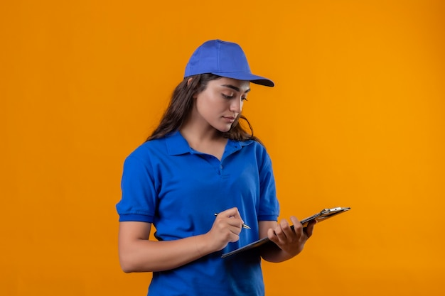 Young delivery girl in blue uniform and cap holding clipboard looking at it writing something with serious face standing over yellow background