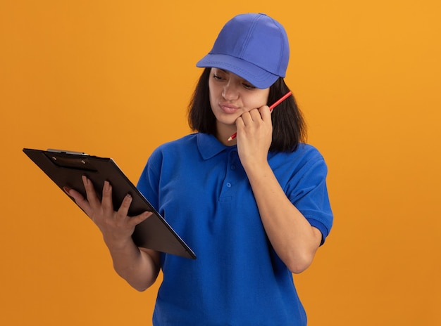 Young delivery girl in blue uniform and cap holding clipboard and pencil looking confused standing over orange wall