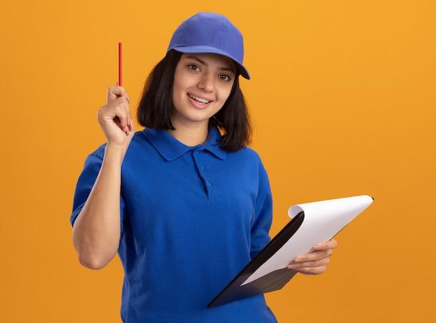 Giovane ragazza di consegna in uniforme blu e cappuccio che tiene appunti con pagine bianche e matita sorridente felice e positivo in piedi sopra la parete arancione