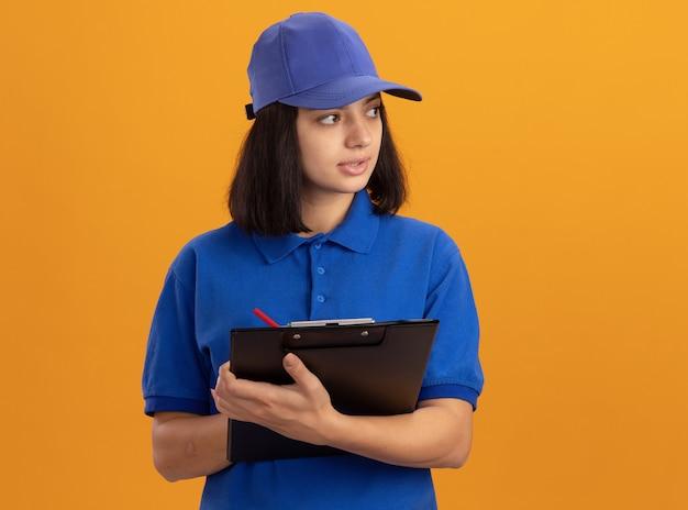 Giovane ragazza di consegna in uniforme blu e cappuccio che tiene appunti con pagine vuote e matita che guarda da parte con la faccia seria che sta sopra la parete arancione