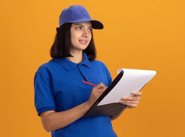 Giovane ragazza di consegna in uniforme blu e cappuccio che tiene appunti con pagine vuote e matita che guarda da parte con il sorriso sul viso in piedi sopra la parete arancione