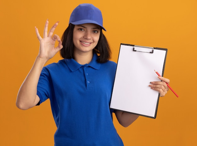 Giovane ragazza di consegna in uniforme blu e cappuccio che tiene appunti con pagine vuote e matita sorridente che mostra segno giusto in piedi sopra la parete arancione