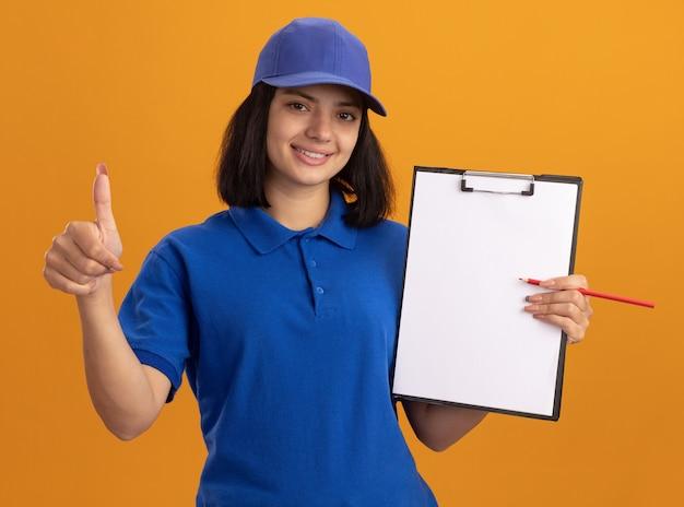 Giovane ragazza di consegna in uniforme blu e cappuccio che tiene appunti con pagine vuote e matita sorridente che mostra i pollici in su in piedi sopra la parete arancione