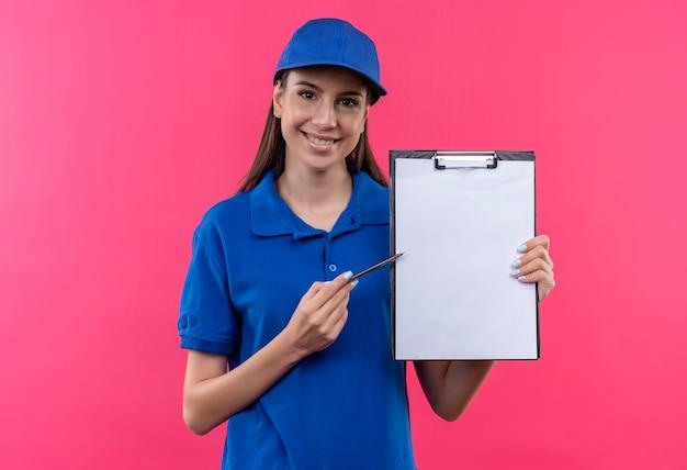 Giovane ragazza di consegna in uniforme blu e cappuccio che tiene appunti con pagine vuote che puntano ad esso con la penna che chiede la firma con il sorriso sul viso