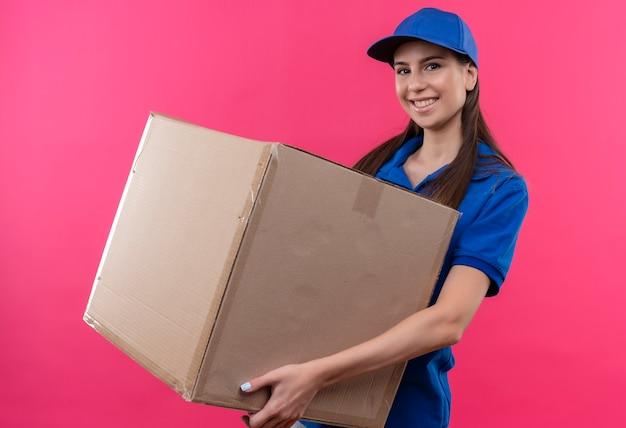 Giovane ragazza delle consegne in uniforme blu e cappuccio che tiene il grande pacchetto della scatola che guarda l'obbiettivo con il sorriso sul fronte