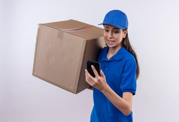 Giovane ragazza di consegna in uniforme blu e cappuccio che tiene grande scatola di cartone guardando lo schermo del telefono cellulare preoccupato e confuso
