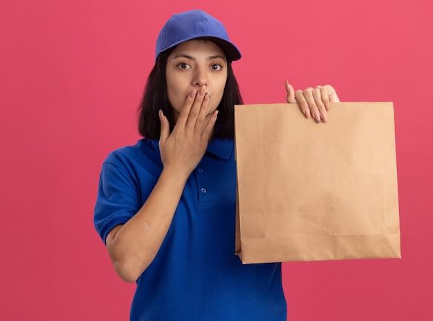 Giovane ragazza di consegna in uniforme blu e cappuccio che tiene il pacchetto di carta che è scioccato che copre la bocca con la mano che sta sopra la parete rosa