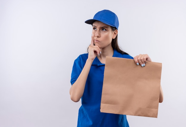 Young delivery girl in blue uniform and cap holding paper package looking aside with pensive expression on face, thinking