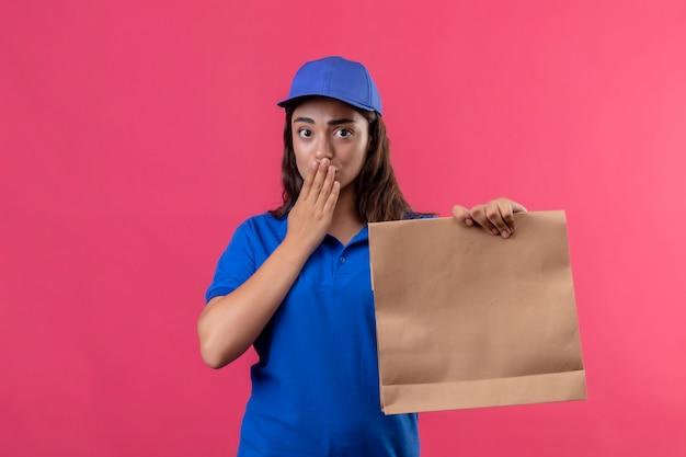 Giovane ragazza di consegna in uniforme blu e cappuccio che tiene il pacchetto di carta che sembra sorpreso che copre la bocca con la mano che sta sopra il fondo rosa