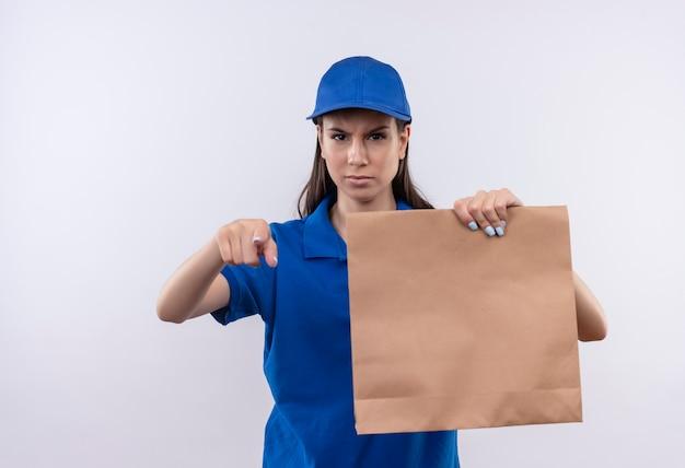 Giovane ragazza di consegna in uniforme blu e cappuccio che tiene il pacchetto di carta che indica con il dito alla macchina fotografica con il fronte accigliato arrabbiato