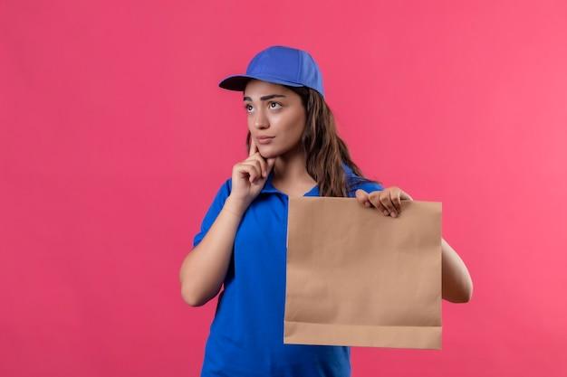 Giovane ragazza di consegna in uniforme blu e cappuccio che tiene il pacchetto di carta in piedi con il dito sul mento con espressione pensierosa sul viso pensando su sfondo rosa