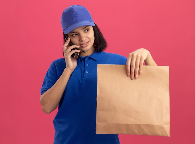 Giovane ragazza di consegna in uniforme blu e cappuccio che tiene il pacchetto di carta parlando al telefono cellulare con il sorriso sul viso in piedi sopra la parete rosa
