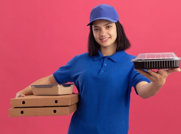 Giovane ragazza delle consegne in uniforme blu e cappuccio che tiene le scatole della pizza e il pacchetto alimentare sorridendo allegramente in piedi sopra il muro rosa