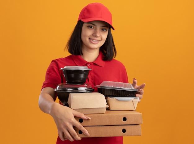 Giovane ragazza di consegna in uniforme blu e cappuccio che tiene le scatole per pizza e il pacchetto di cibo che sorride in piedi felice e positivo sopra la parete arancio