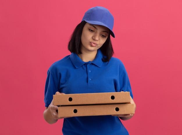 Giovane ragazza delle consegne in uniforme blu e cappuccio che tiene le scatole della pizza che sembra scontenta dell'espressione triste che sta sopra la parete rosa