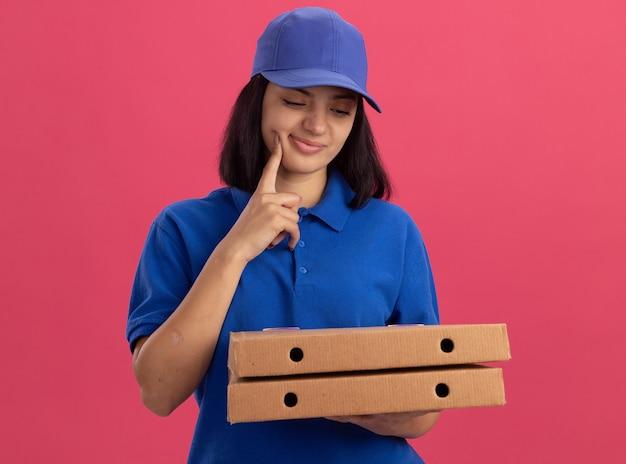 Giovane ragazza delle consegne in uniforme blu e cappuccio che tiene le scatole per pizza guardandole pensando in piedi sul muro rosa