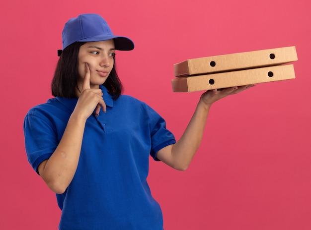 Giovane ragazza delle consegne in uniforme blu e cappuccio che tiene le scatole per pizza guardandole con espressione pensierosa pensando in piedi sopra il muro rosa