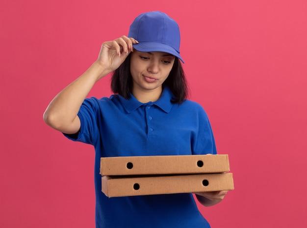 Giovane ragazza delle consegne in uniforme blu e cappuccio che tiene le scatole per pizza facendo la bocca ironica con espressione delusa in piedi sopra la parete rosa