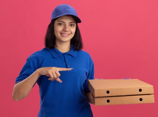 Giovane ragazza delle consegne in uniforme blu e cappuccio che tiene le scatole per pizza che punta con il dito indice a lato sorridente in piedi sopra la parete rosa