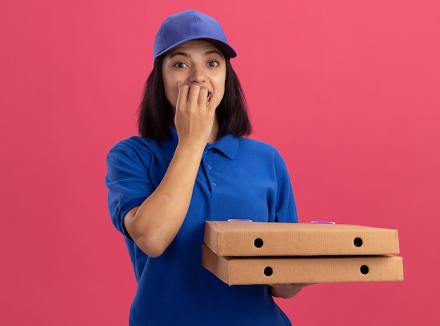 Giovane ragazza delle consegne in uniforme blu e cappuccio che tiene le scatole della pizza stressata e nervosa che si morde le unghie in piedi sopra il muro rosa