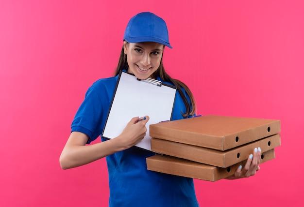 Giovane ragazza di consegna in uniforme blu e cappuccio che tiene pila di scatole per pizza e appunti con pagine vuote che chiedono la firma