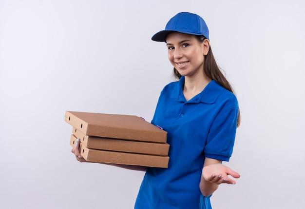 Giovane ragazza di consegna in uniforme blu e cappuccio che tiene pila di scatole per pizza guardando la telecamera sorridendo allegramente allungando il braccio chiedendo il pagamento