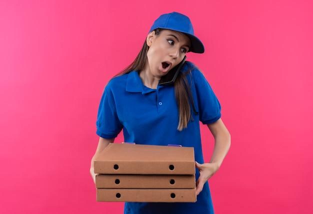Giovane ragazza delle consegne in uniforme blu e cappuccio che tiene la pila di scatole per pizza che sembra sorpresa mentre parla al telefono cellulare