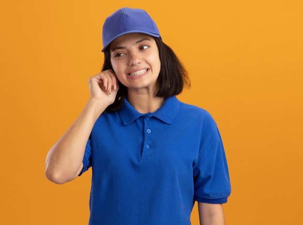 Young delivery girl in blue uniform and cap looking aside confused standing over orange wall