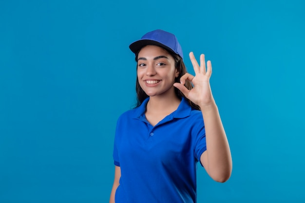 Young delivery girl in blue uniform and cap looking at camera smiling cheerfully doing ok sign standing over blue background