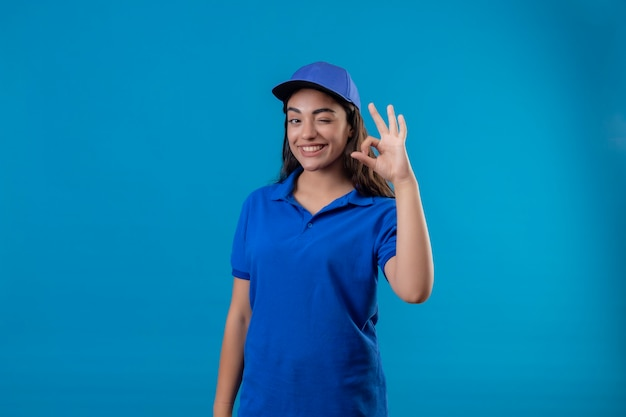 Young delivery girl in blue uniform and cap looking at camera winking smiling cheerfully doing ok sign standing over blue background