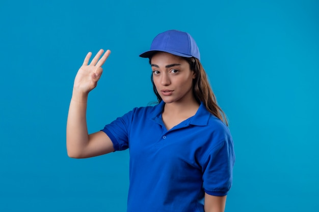 Young delivery girl in blue uniform and cap looking at camera with sad expression on face doing ok sign standing over blue background