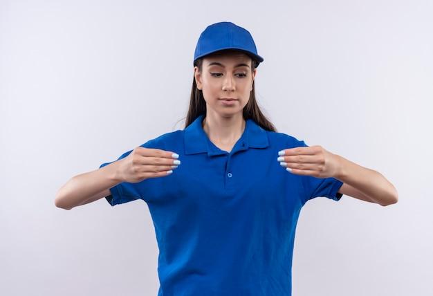 Giovane ragazza delle consegne in uniforme blu e berretto cercando fiducioso gesticolando con le mani, il concetto di linguaggio del corpo