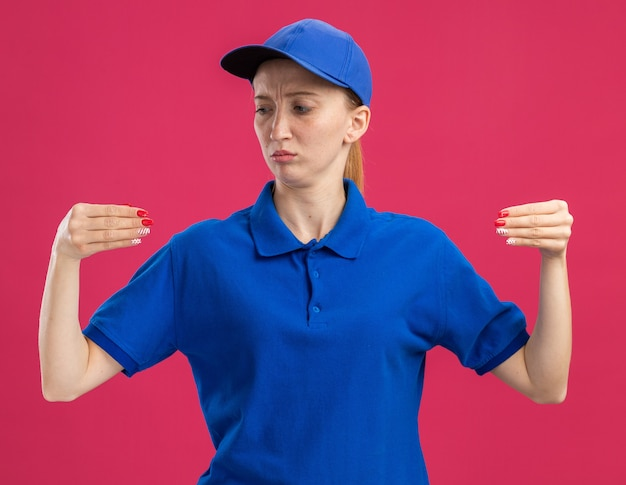 Young delivery girl in blue uniform and cap looking confident gesturing with hands like holding something standing over pink wall