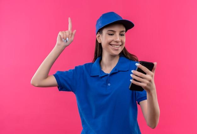 Giovane ragazza delle consegne in uniforme blu e cappuccio guardando lo schermo del suo telefono cellulare che punta con il dito verso l'alto avendo grande idea felice