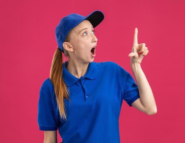 Giovane ragazza delle consegne in uniforme blu e berretto che guarda stupito e sorpreso indicando con il dito indice qualcosa in piedi sul muro rosa pink