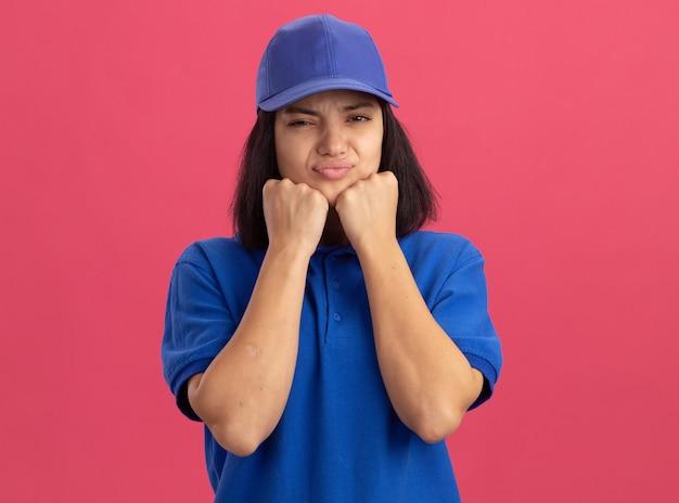 Giovane ragazza di consegna in uniforme blu e cappuccio che fa la bocca ironica con espressione delusa in piedi sopra il muro rosa