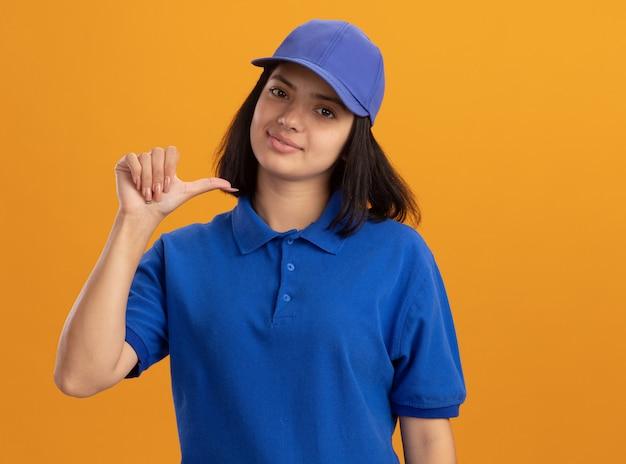 Giovane ragazza delle consegne in uniforme blu e berretto pointgn a se stessa sorridente fiducioso in piedi sopra la parete arancione