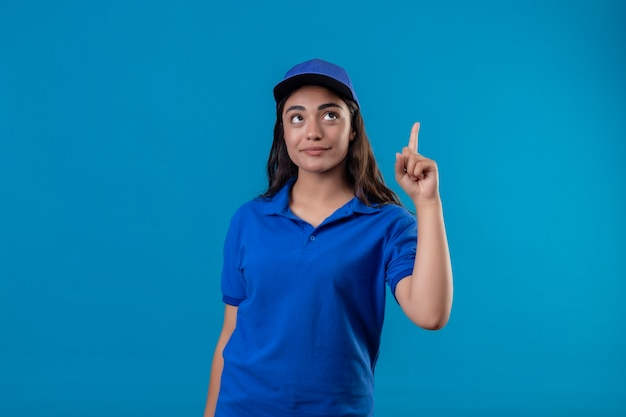 Young delivery girl in blue uniform and cap pointing finger up concentrated on a task standing over blue background