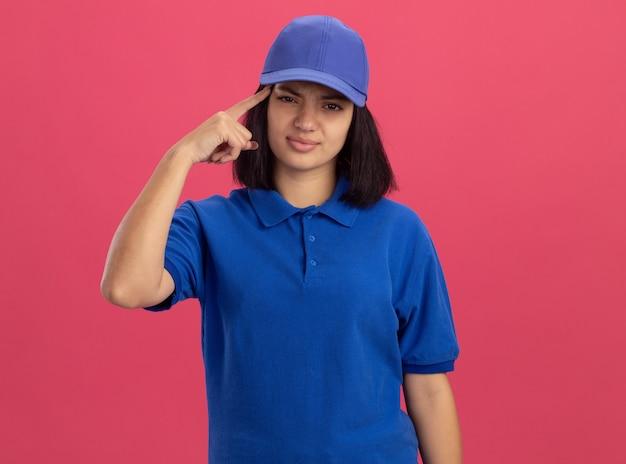 Giovane ragazza delle consegne in uniforme blu e cappuccio che punta con il dito indice alla tempia in piedi sopra il muro rosa