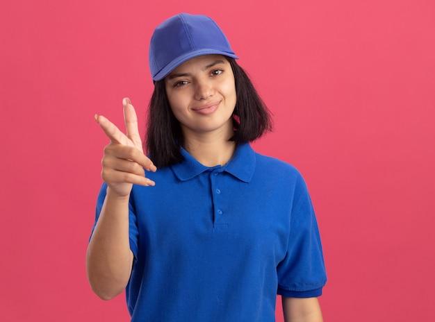 Giovane ragazza delle consegne in uniforme blu e cappuccio che punta con il dito indice sorridente in piedi amichevole sopra la parete rosa