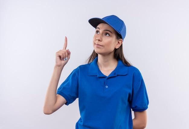 Giovane ragazza delle consegne in uniforme blu e cappuccio che indica con il dito indice in alto con un'espressione seria sicura sul viso