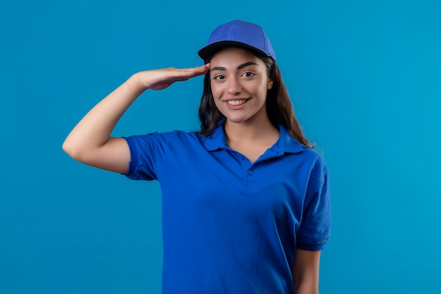 Young delivery girl in blue uniform and cap saluting looking at camera with confident smile on face standing over blue background
