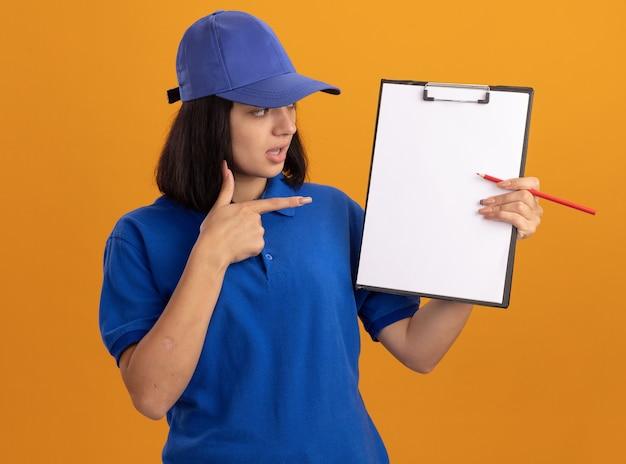 Giovane ragazza di consegna in uniforme blu e cappuccio che mostra appunti con pagine vuote e matita che punta con il dito indice a loro confuso in piedi sopra la parete arancione