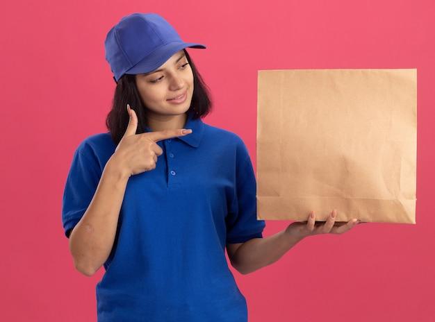 Giovane ragazza delle consegne in uniforme blu e cappuccio che mostra il pacchetto di carta che punta con il dito indice sorridendo fiducioso in piedi sopra il muro rosa