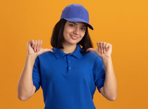 Giovane ragazza di consegna in uniforme blu e berretto sorridente pointign fiducioso a se stesso in piedi sopra la parete arancione