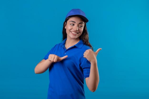 Giovane ragazza di consegna in uniforme blu e cappello sorridente fiducioso che punta al lato con i pollici in piedi su sfondo blu