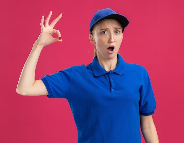 Giovane ragazza delle consegne in uniforme blu e berretto sorpreso mostrando segno ok in piedi sul muro rosa