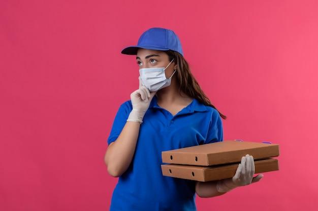 Giovane ragazza delle consegne in uniforme blu e cappuccio che indossa la maschera protettiva per il viso e guanti tenendo le scatole per pizza guardando da parte con espressione pensierosa pensando in piedi su sfondo rosa